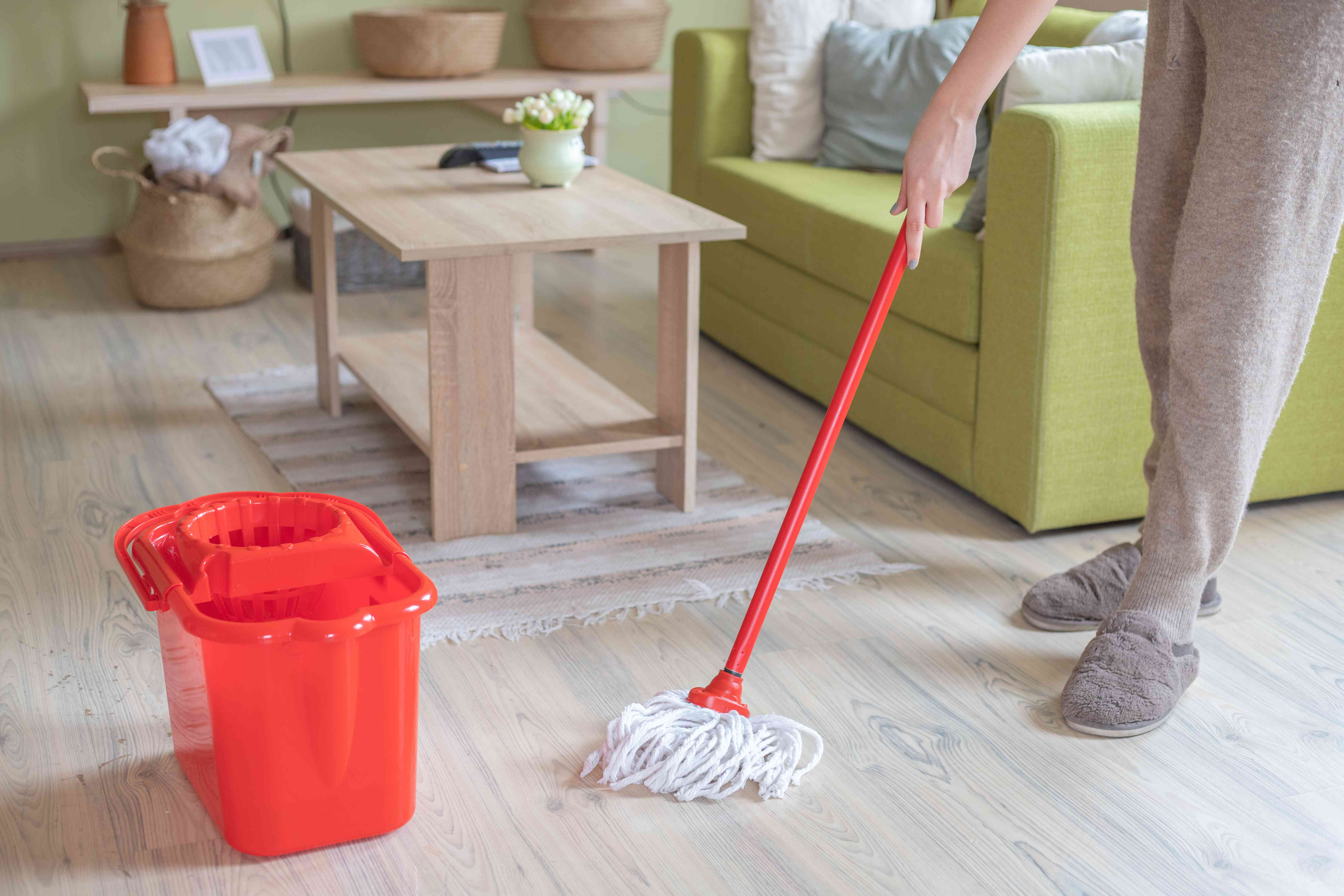 waist-down shot of person cleaning house with red bucket and mop