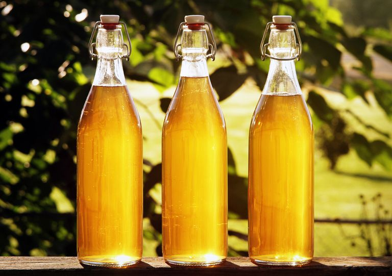 Three bottles of honey mead sitting on a wooden railing