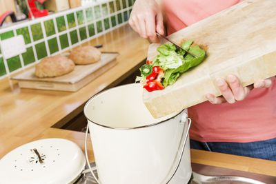 Woman scraping vegetable scraps into a compost caddy