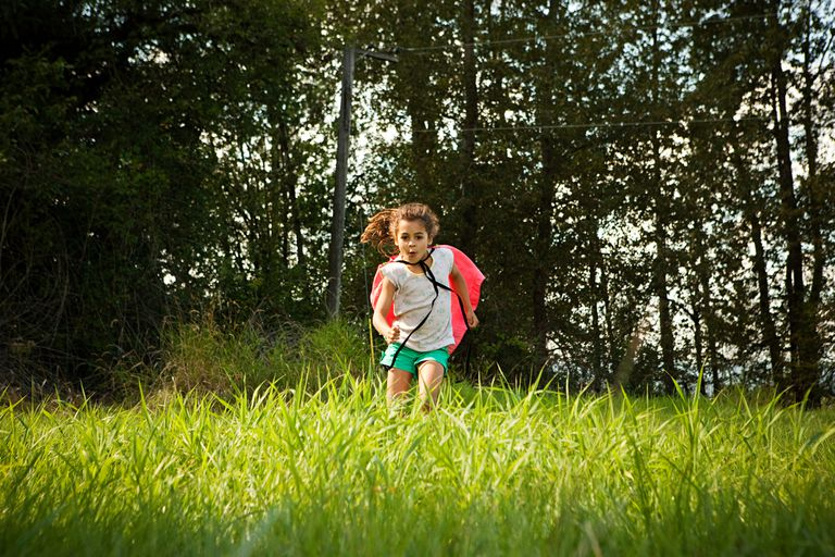 Girl running in a field wearing a cape