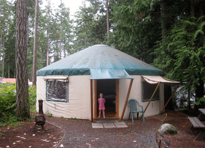 A kid stands in the doorway of a yurt