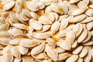 A pile of raw pumpkin seeds with some orange pulp.