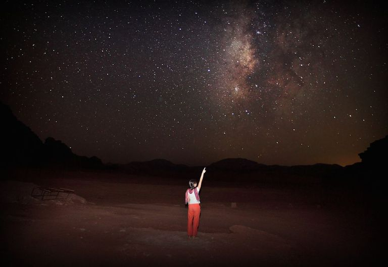 Woman pointing up to the dark, starry night sky