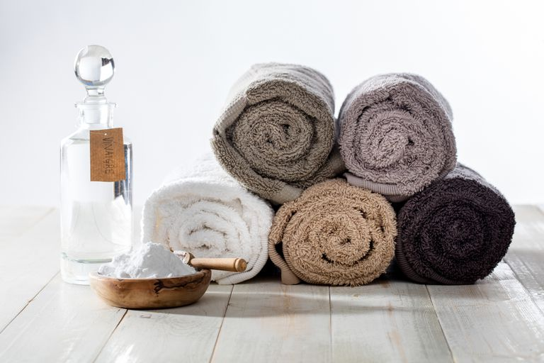 rolled towels with bottle of vinegar and baking soda