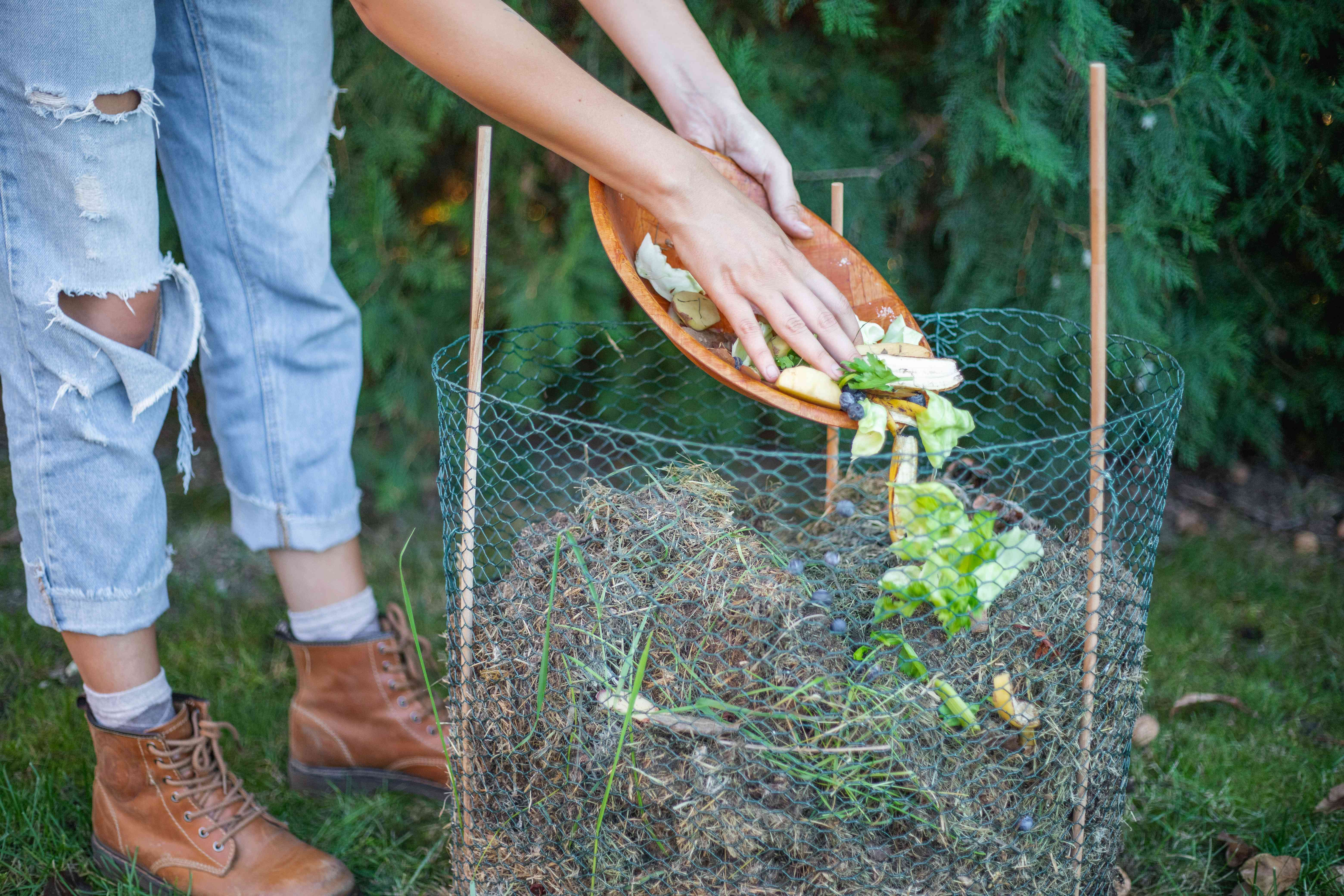 woman in torn jeans tosses old food scraps into cold compost system outside