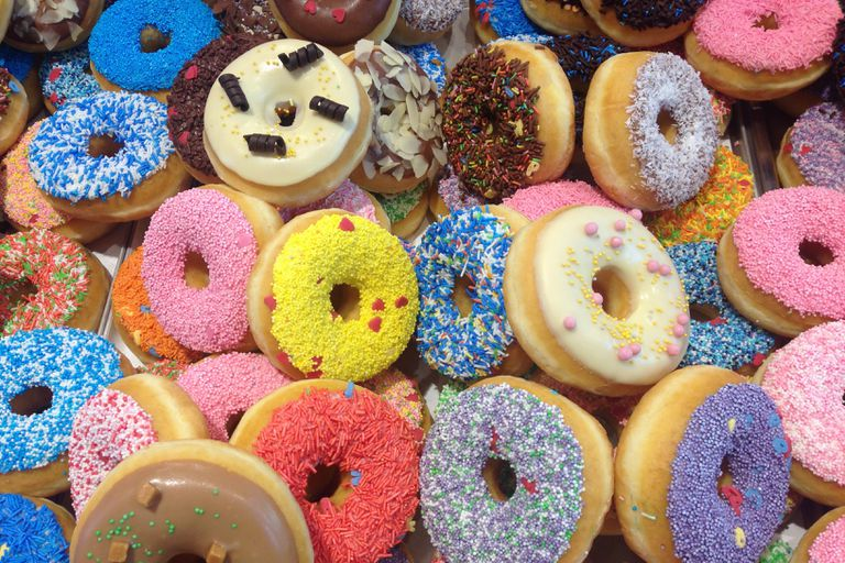 Trays of donuts with brightly colored sprinkles
