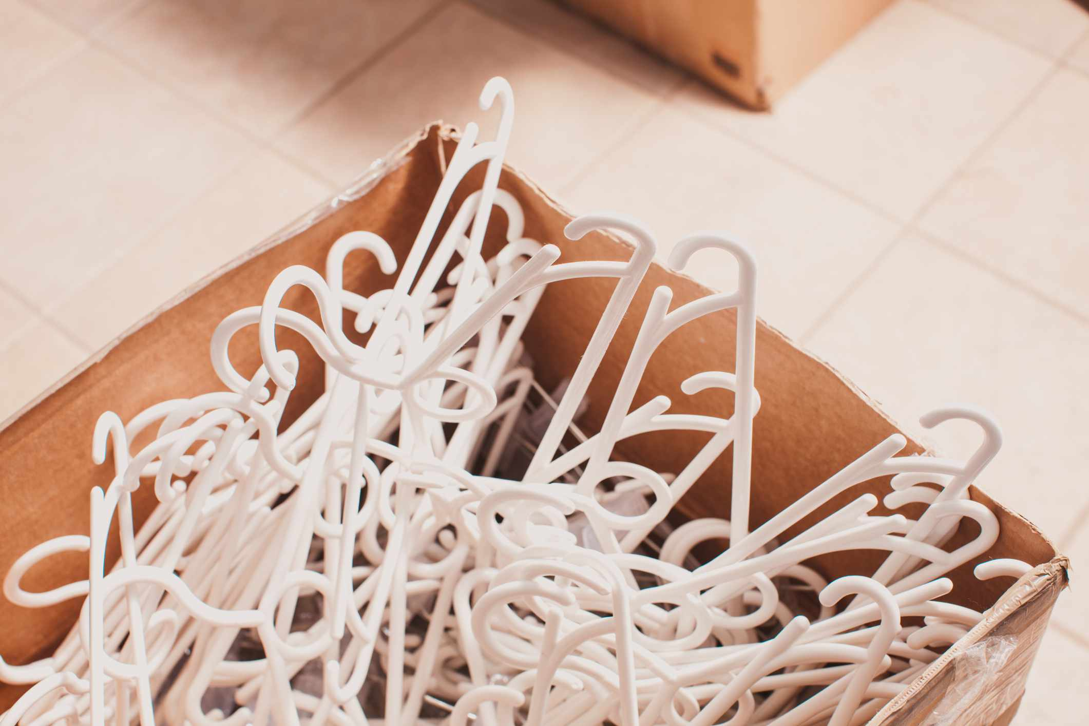White plastic clothing hangers piled in a box.