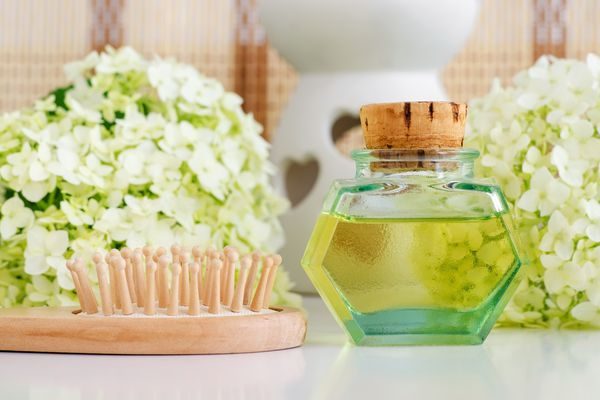 Vintage glass bottle with cosmetic oil (massage oil, tincture, infusion, extract), wooden hairbrush and white hortensia (hydrangea) flowers. Aromatherapy, homemade spa and herbal medicine concept. Copy space.