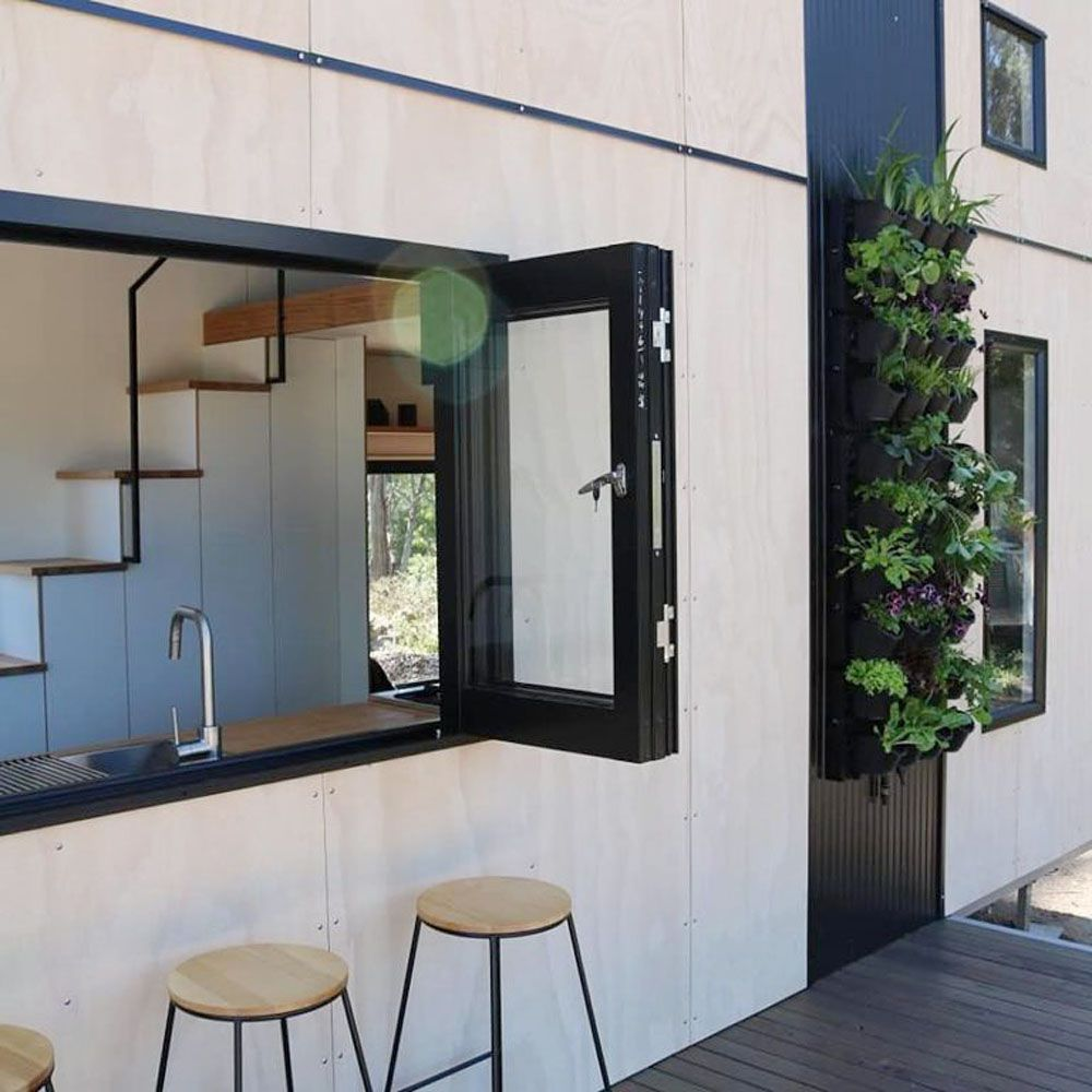Exterior of house with open kitchen window and bar stools sitting along the opening