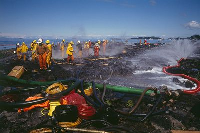 Teams of firefighters cleaning the Alaskan coast following the Exxon Valdez oil spill.