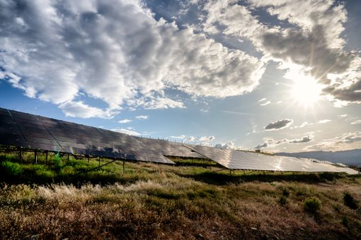 A Solar Farm In Western Colorado Near Sunset With The Sun, Blue Sky And Clouds Reflecting Down On The Solar Panels