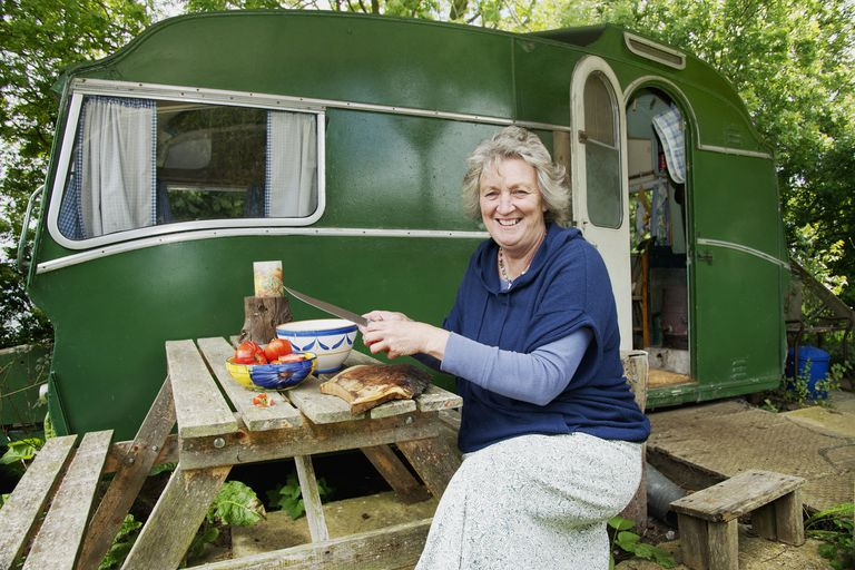 A happy senior woman sitting outside of a green vintage trailer.