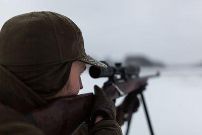 Deer hunter aiming with a gun