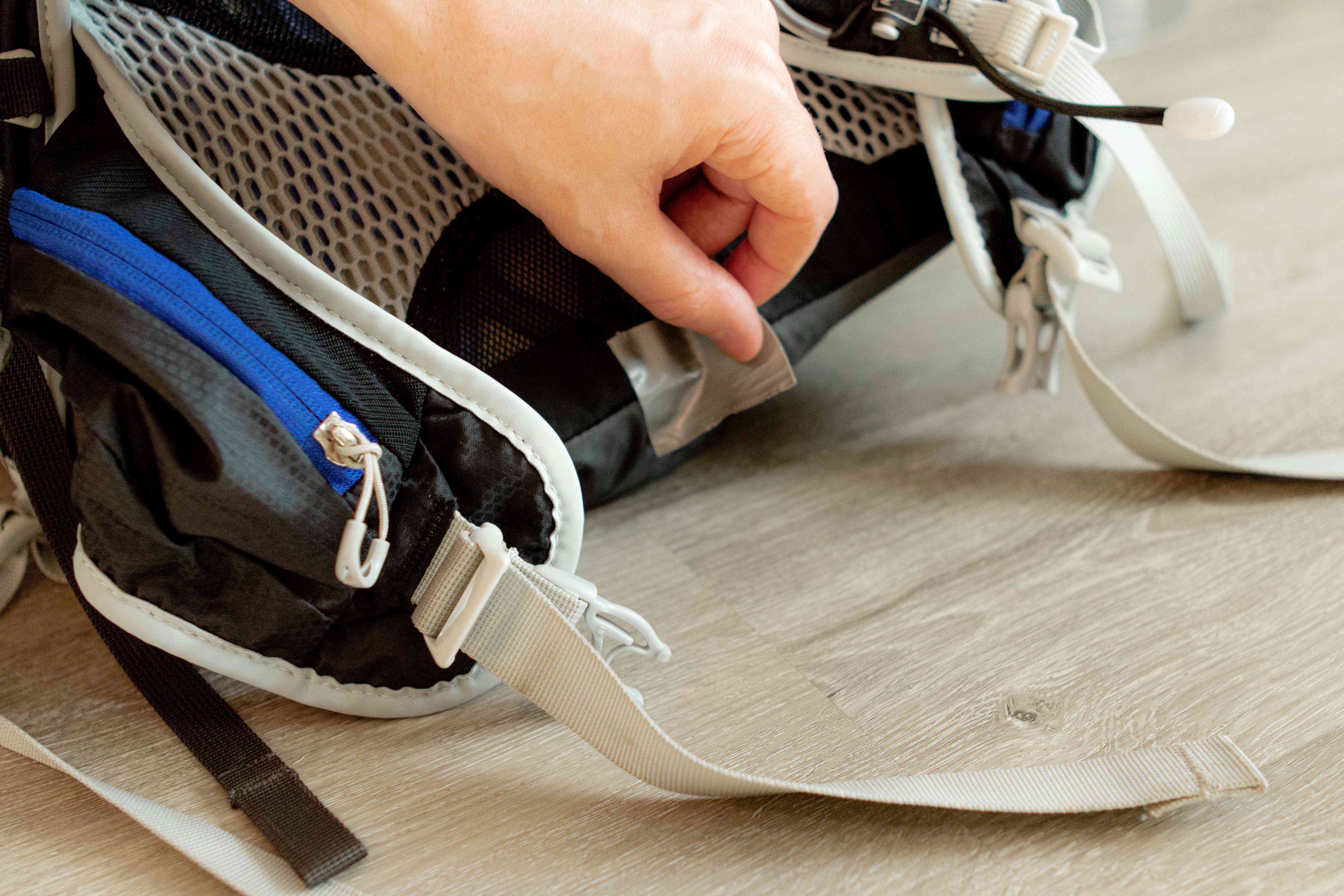 hand uses duct tape to repair bottom of backpack