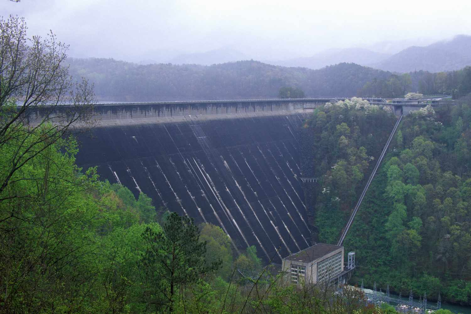 The Fontana Dam stretches across the Little Tennessee River with green deciduous trees growing on each side