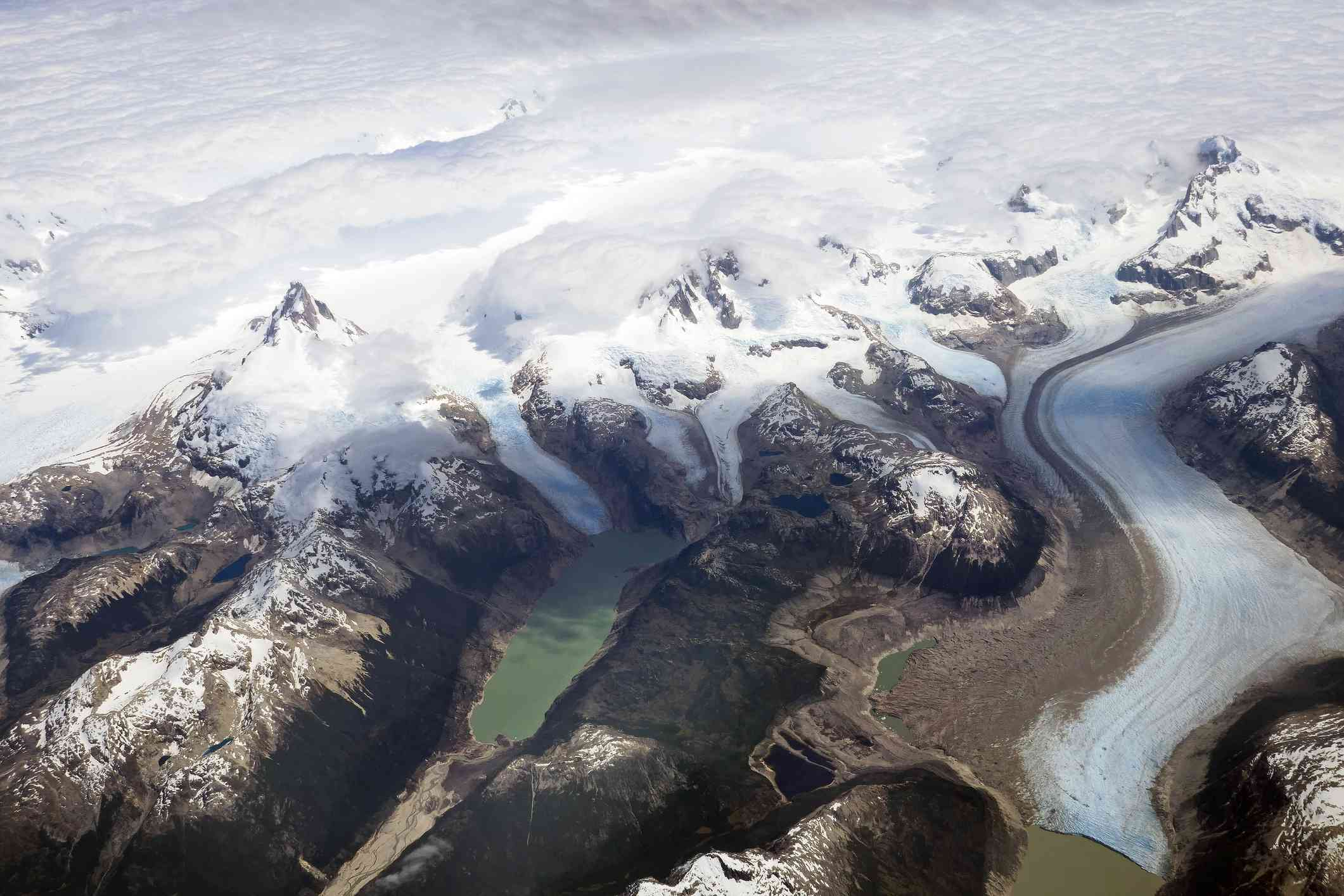 An aerial photo of a gray-green lake dammed by the arm of a large glacier