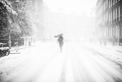 Pedestrian cross street in snow blizzard.
