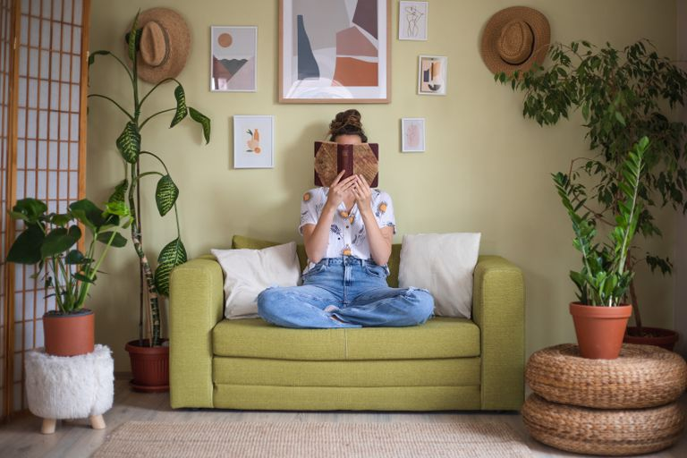 woman reads book on green couch surrounded by various large house plants