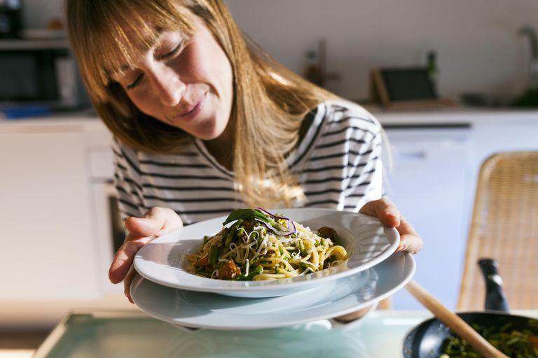 woman with bowl of vegan pasta