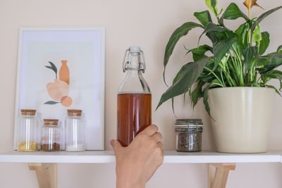 hand reaches for flip-top glass jar of ACV on floating kitchen shelf