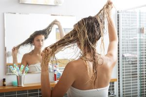 A blonde white woman pulls her wet hair in the bathroom mirror.