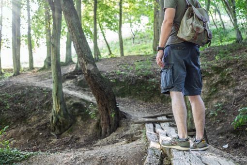 guy outside hiking with backpack pauses on old wooden trail to admire trees