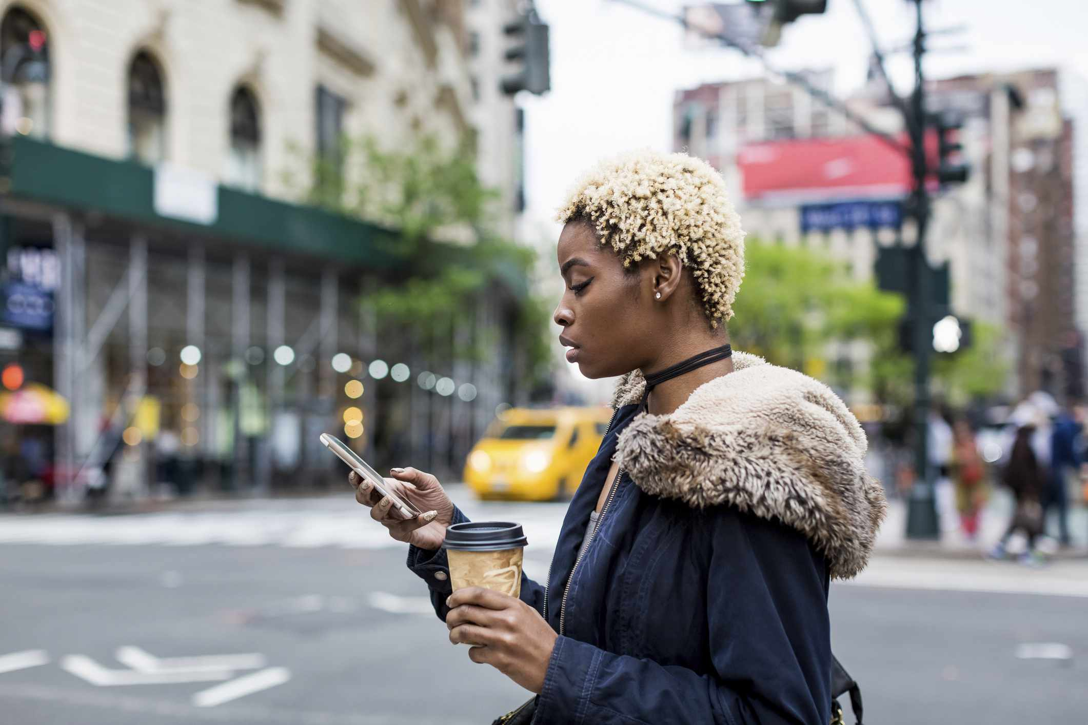 A young black woman crosses the street looking at phone in New York City.