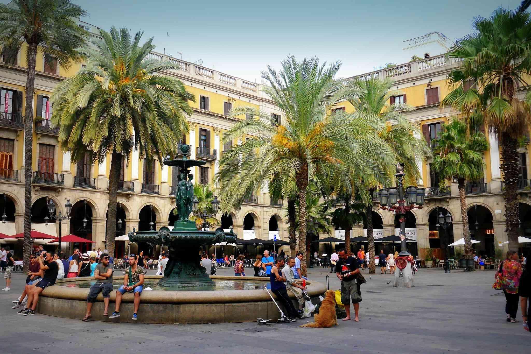 People sitting around fountain in Plaça Reial, Barcelona