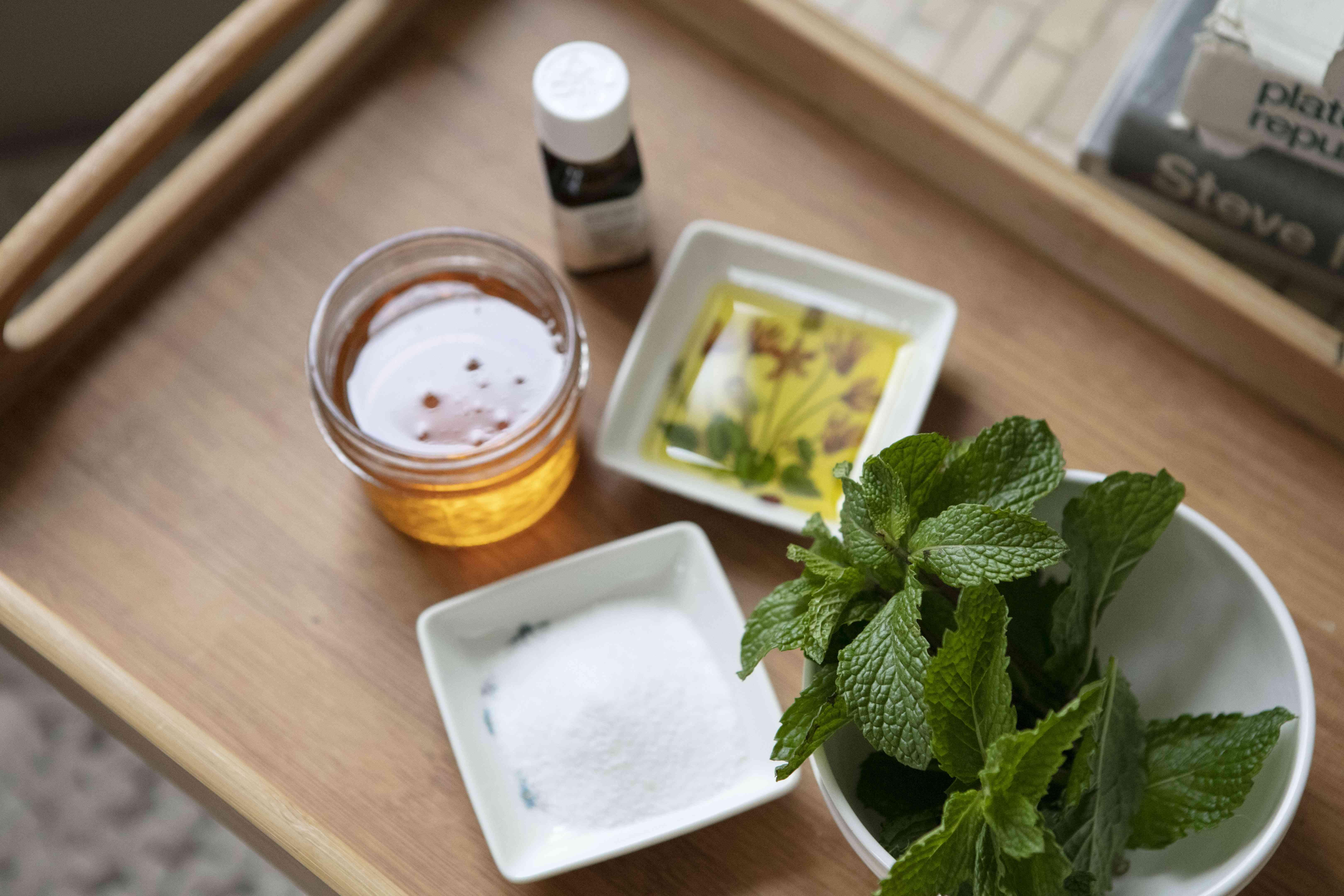 fresh mint, sugar, olive oil, and honey on a wooden tray for DIY lip scrub