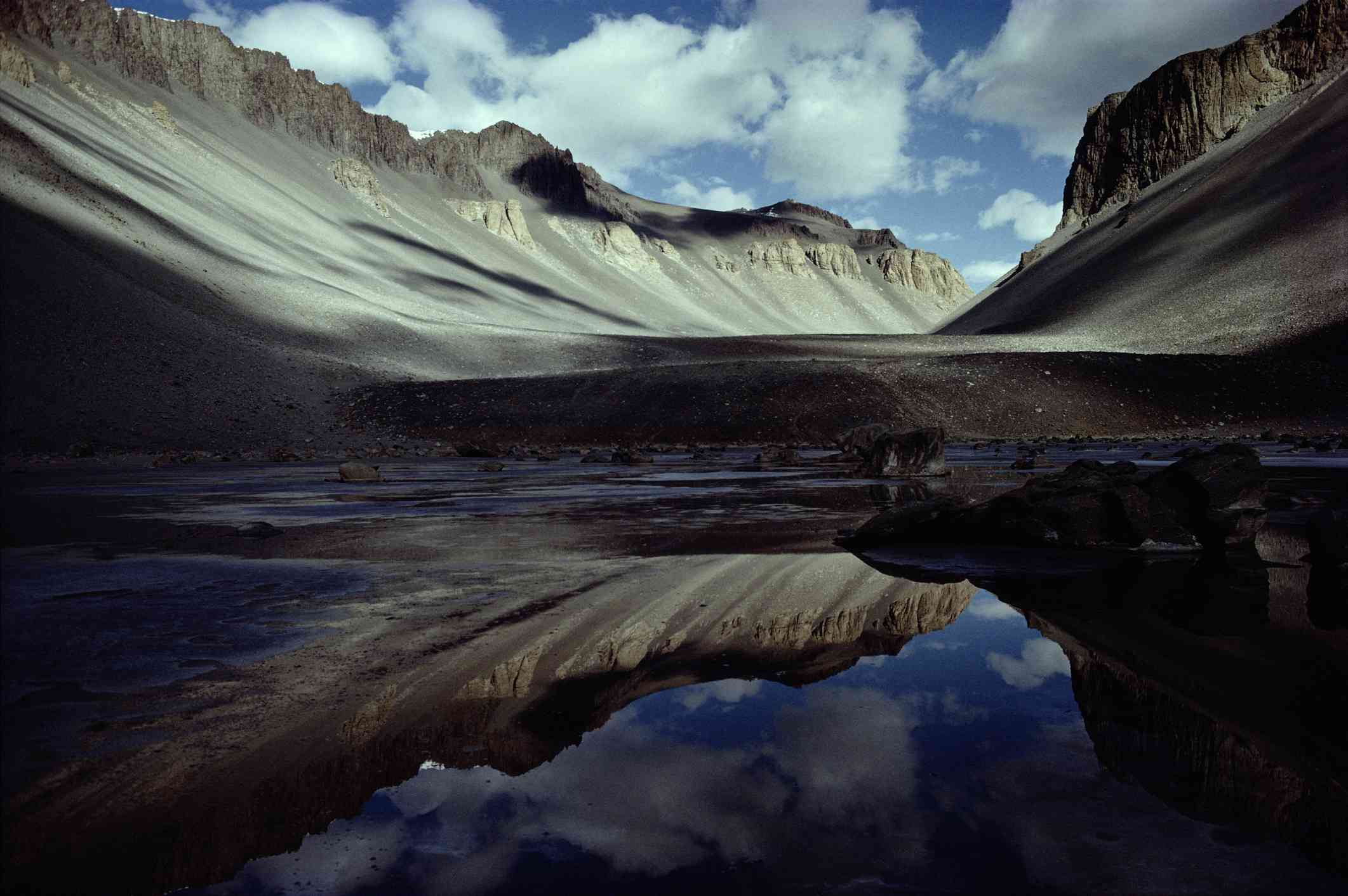 Gray rocky mountains reflected in the waters of a small pond