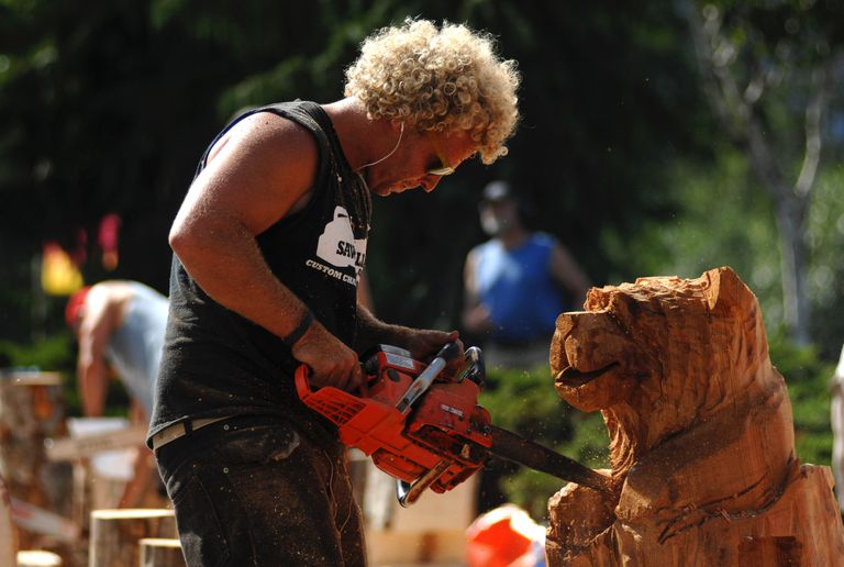 person carves bear with chainsaw
