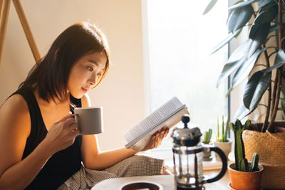 Woman reading a book by plants