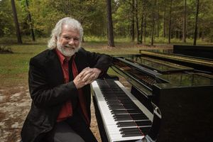 Musician Chuck Leavell at his piano in the woods.