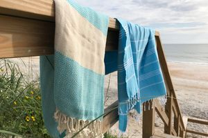 2 Turkish towels hanging on a railing at the beach