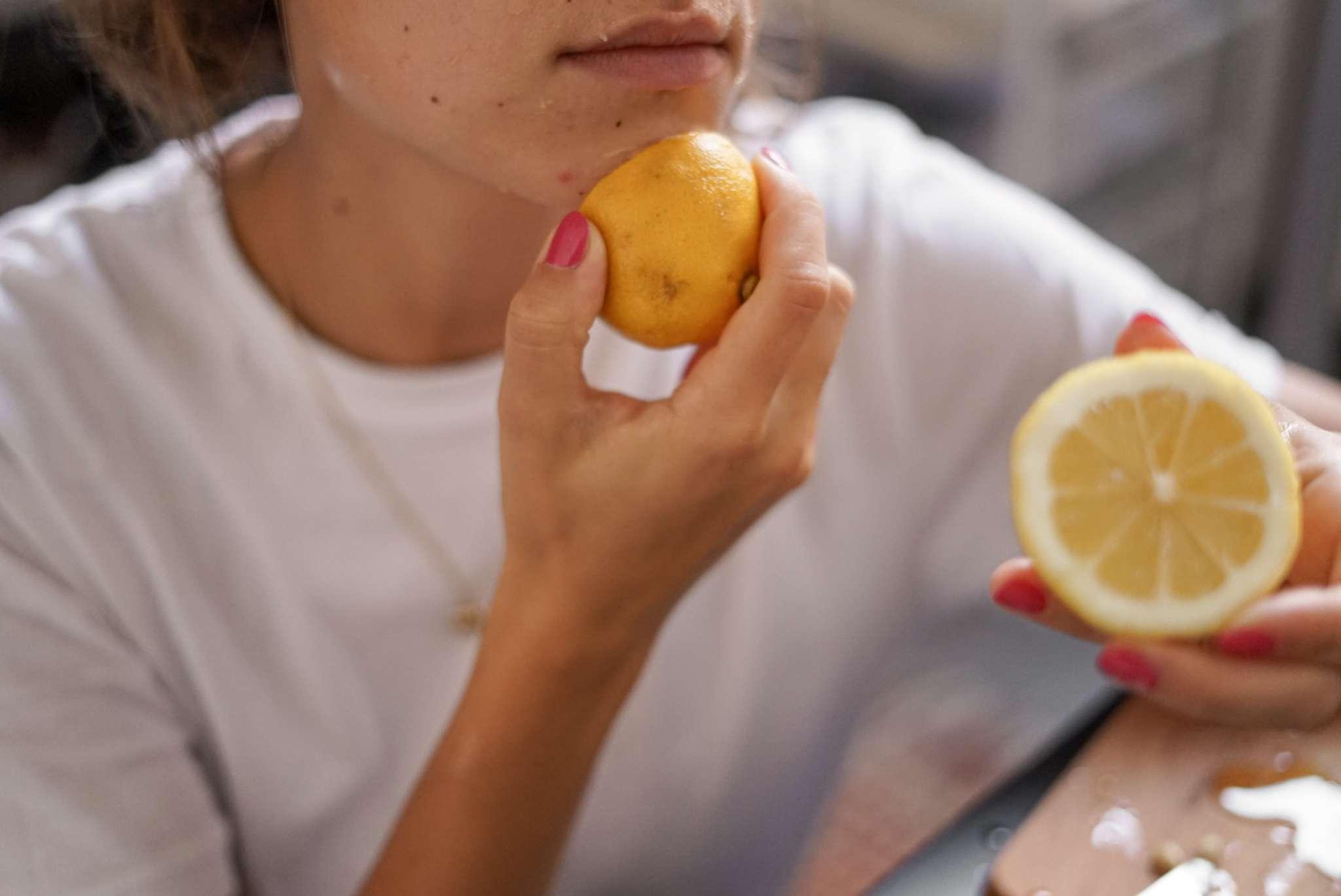women rubs honey and cut lemon on face as natural beauty treatment