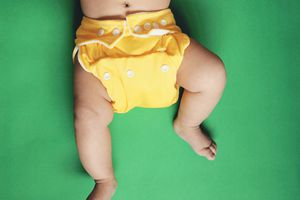 baby in yellow cloth diaper