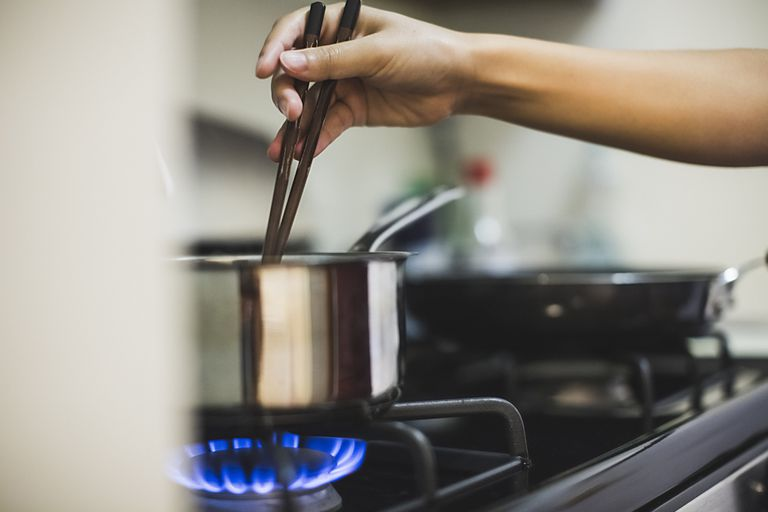 Hand stirring a stainless steel pot on a gas stove burner