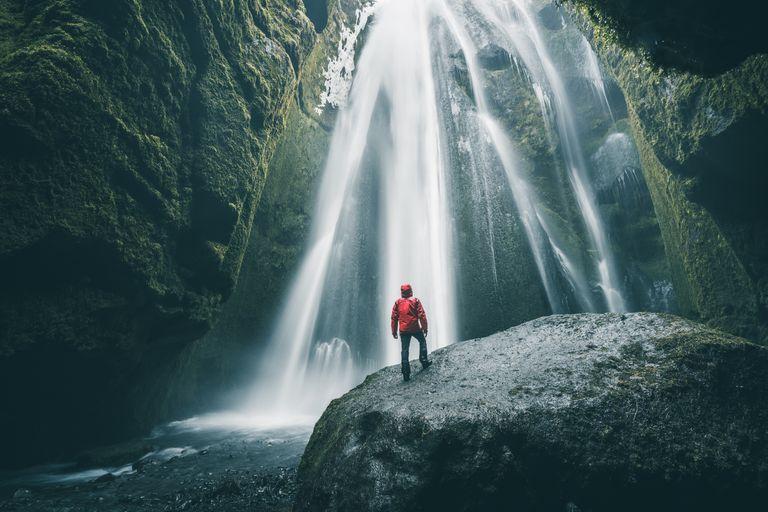Tourist on a rock admiring Gljufrabui waterfall, Iceland