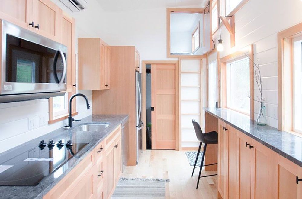 Kitchen counter and cabinets on the left, narrow counter against a window on the right