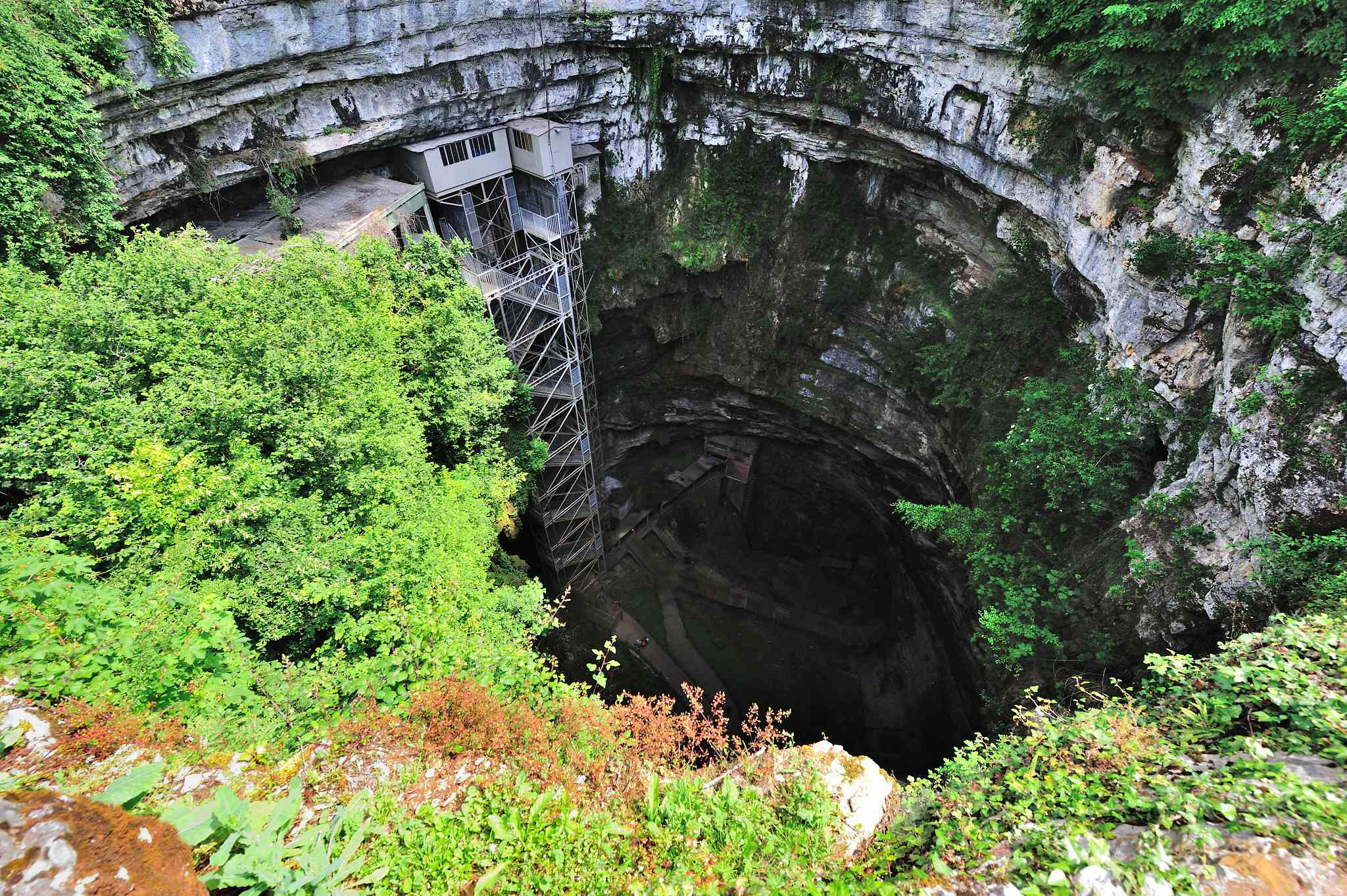The opening of Padirac Cave in France with greenery growing around it