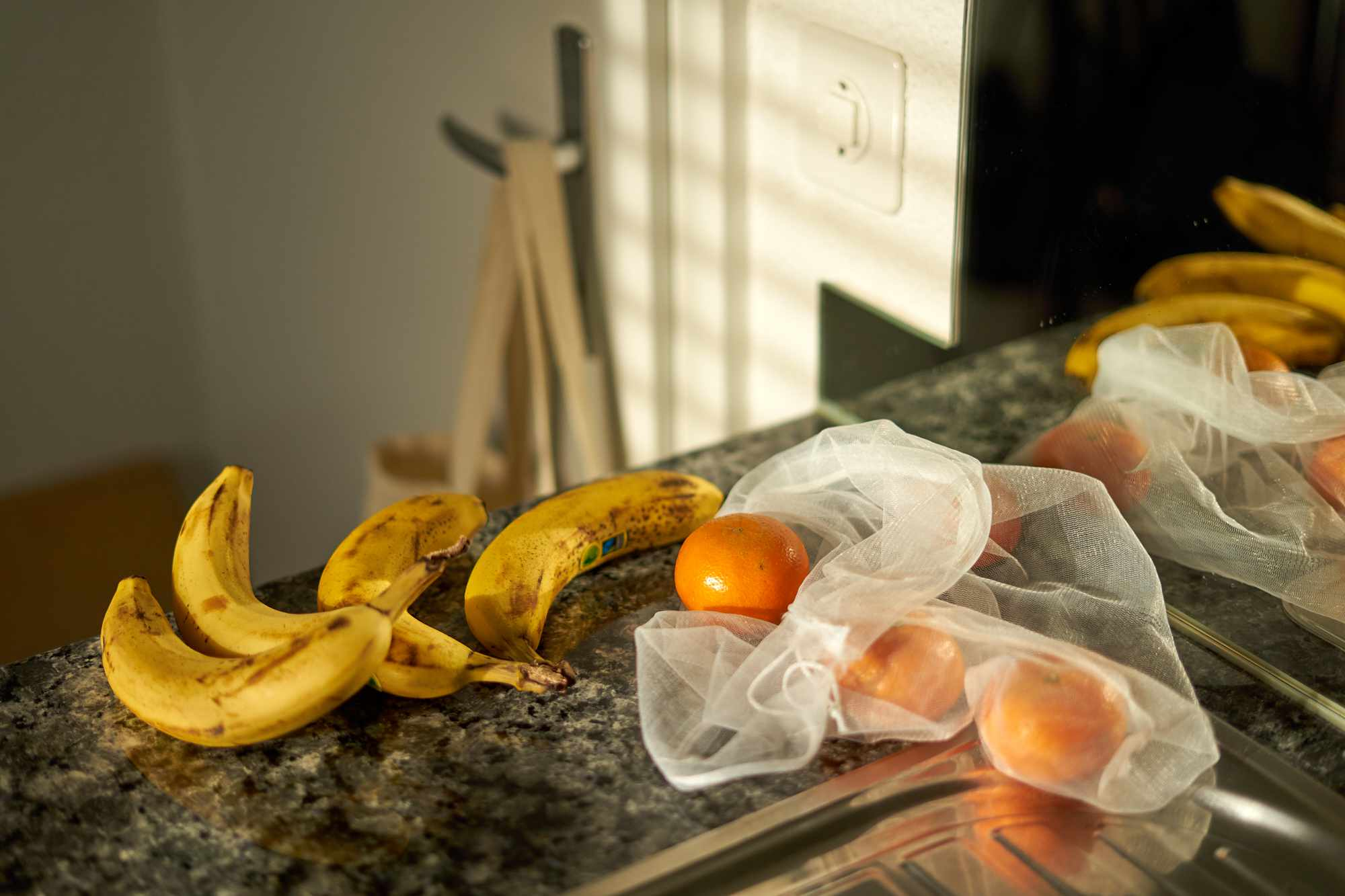 reusable mesh shopping bag with oranges and bananas on kitchen counter