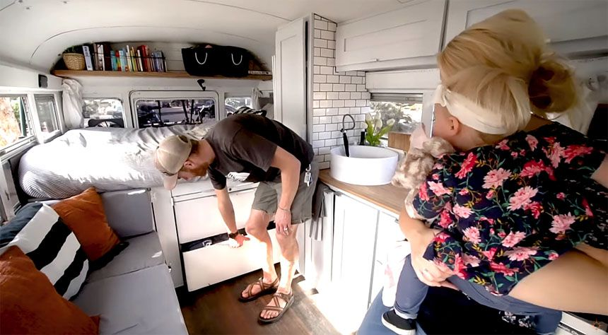 Family showing under bed storage in the converted bus