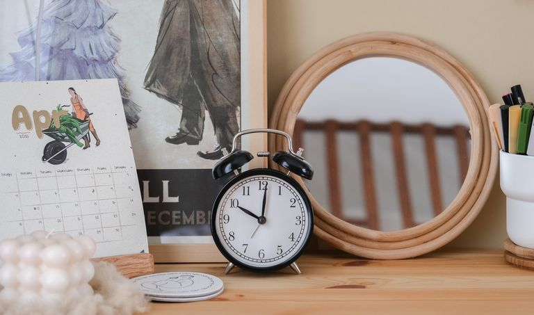 wooden dresser with a calendar and old-fashioned alarm clock to connote time passed