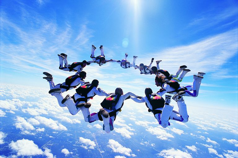 A group of skydivers holding hands to form a circle in the blue sky.