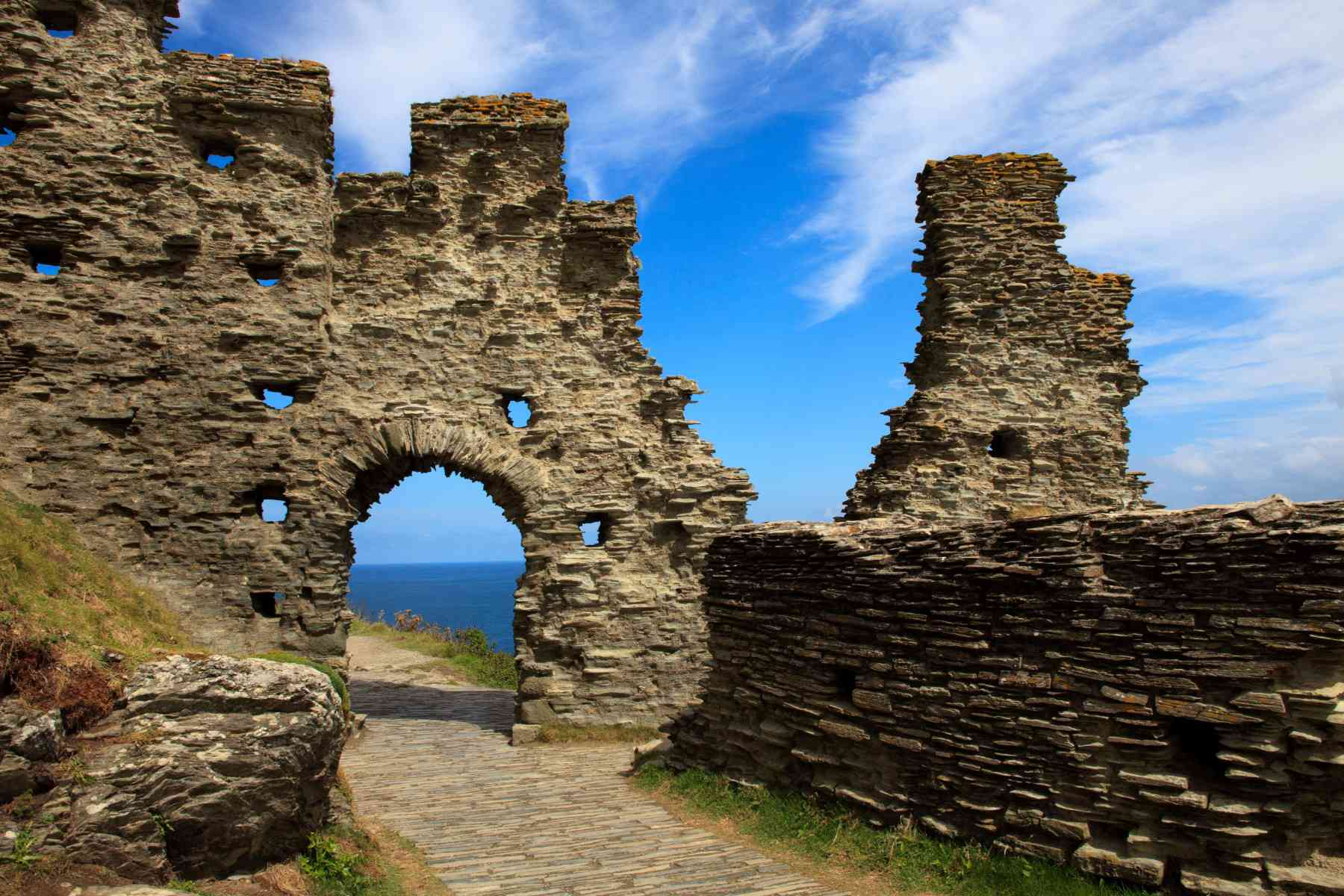 The ruins of Tintagel Castle in England on a partly cloudy day