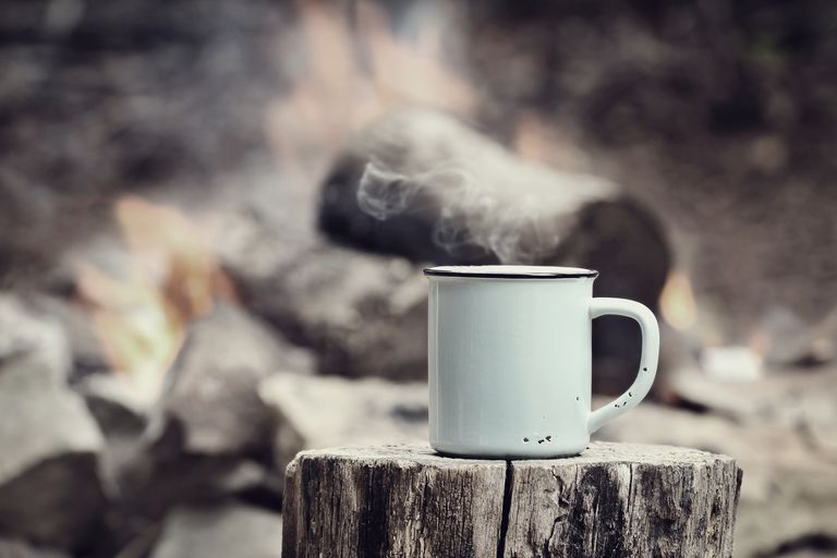 A mug full of steaming hot coffee at a campsite.