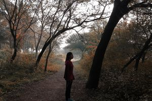 Woman standing in the middle of the woods, looking lost