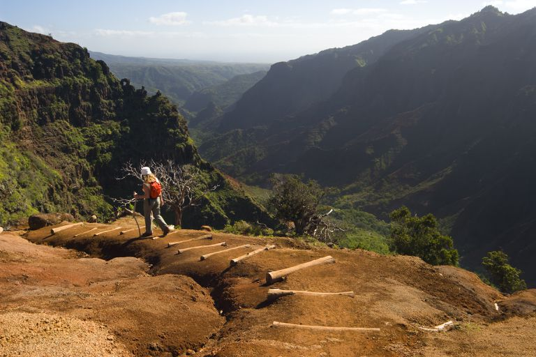 Hiker descending into Waimea Canyon on Kauai, Hawaii