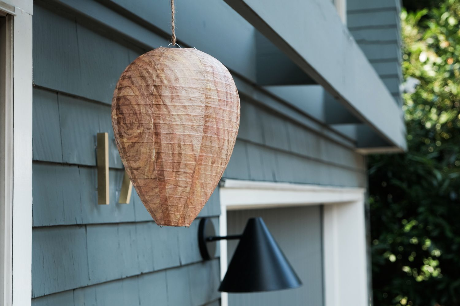 a fake hornets nest hangs outside house to prevent wasps and hornets from making real nest