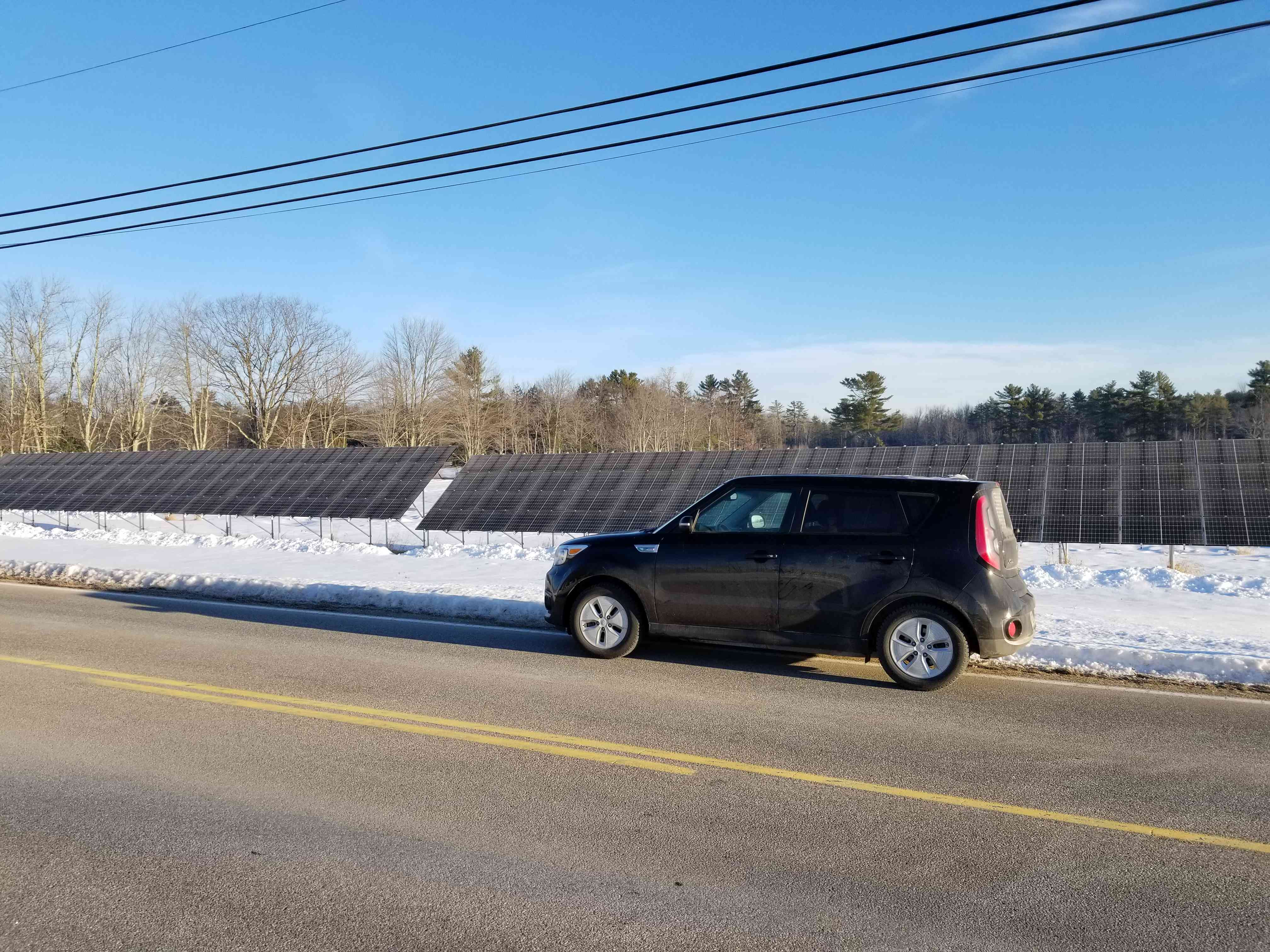 Electric Kia Soul in front of solar panels